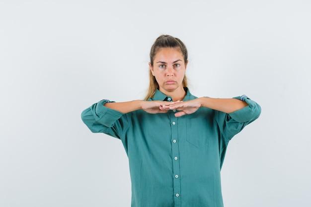 De jonge vrouw die haar combineert overhandigt haar borst in blauw overhemd en kijkt ernstig