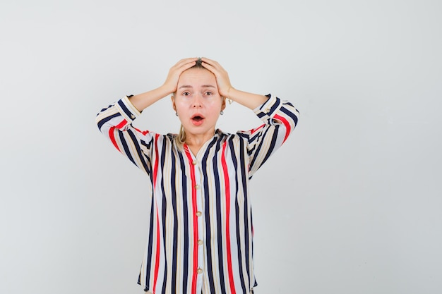 De jonge vrouw die haar hoofd bedekt met haar dient gestreepte blouse in en kijkt geschokt