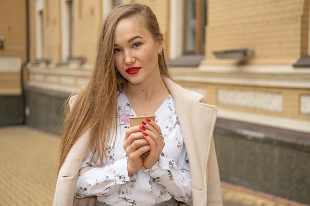 De jonge vrouw die in de straat van de de herfststad lopen en drinken haalt koffie in document kop weg.