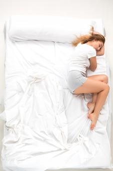 De jonge vrouw die in een bed ligt