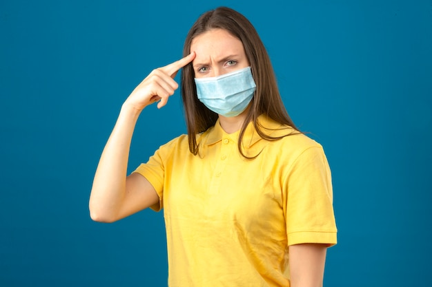 De jonge vrouw die in geel polooverhemd en medisch beschermend masker met vinger aan haar hoofd ontevreden richten kijkt op geïsoleerde blauwe achtergrond