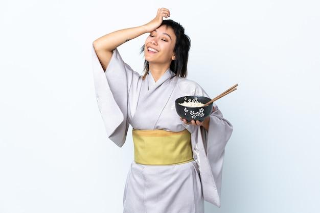 De jonge vrouw die kimono draagt die een kom noedels over witte muur houdt heeft iets gerealiseerd en van plan de oplossing