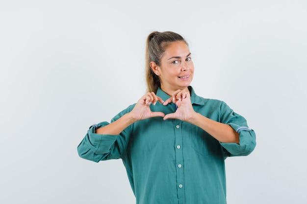 De jonge vrouw die liefdegebaar met handen in groene blouse toont en leuk kijkt