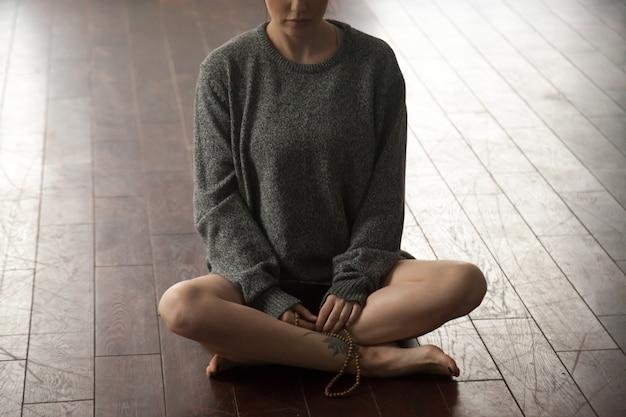 De jonge vrouw die met parels in sukhasana zit stelt
