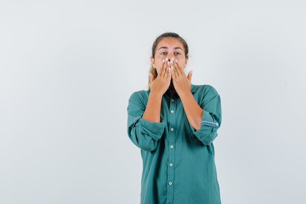 De jonge vrouw die mond behandelt met dient groene blouse in en verrast het kijken