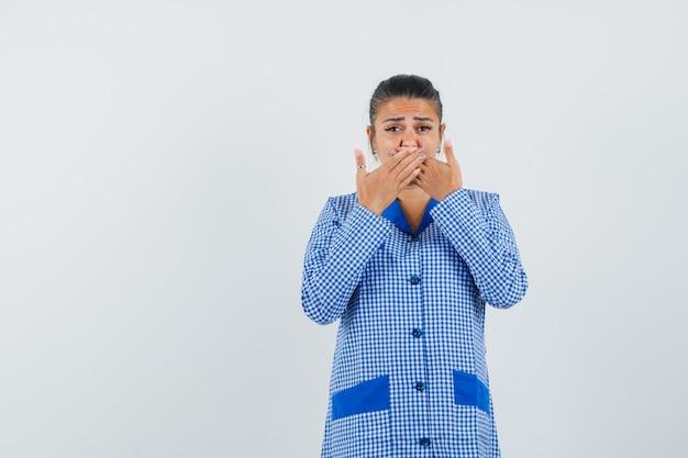 De jonge vrouw die mond behandelt met dient het blauwe overhemd van de gingangpyjama in en spijtig, vooraanzicht kijkt.