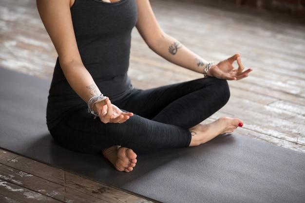 De jonge vrouw die oefening sukhasana doet, sluit omhoog
