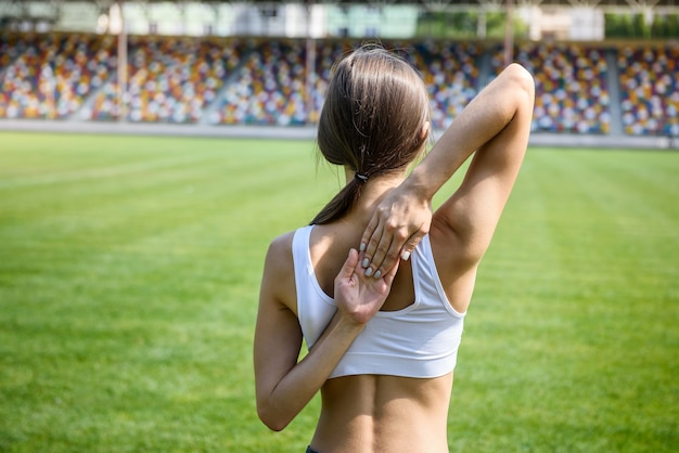 De jonge vrouw die oefeningen met handen over haar rug maakt