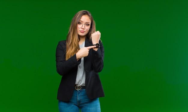 De jonge vrouw die ongeduldig en boos kijkt, wijzend op horloge, die om stiptheid vraagt, wil op tijd op groen zijn