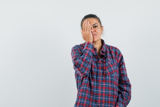 De jonge vrouw die oog behandelt dient gecontroleerd overhemd in en kijkt ernstig, vooraanzicht.