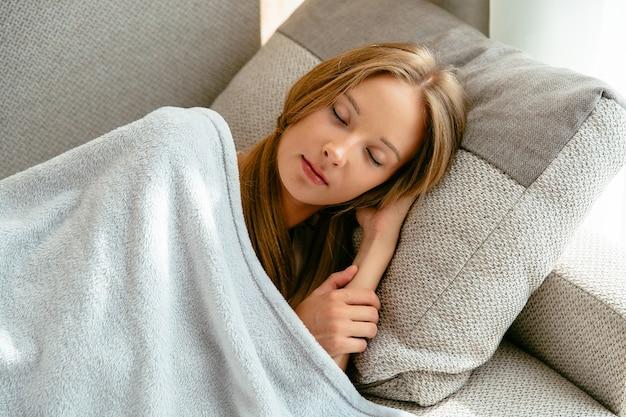 De jonge vrouw die op bank liggen thuis, rust en slapend behandelde blauwe warme deken