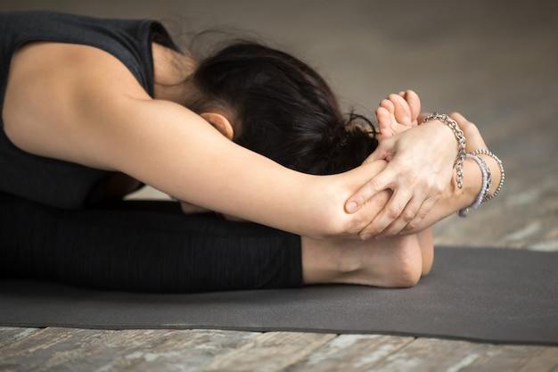 De jonge vrouw die paschimottanasana oefening doet, sluit omhoog