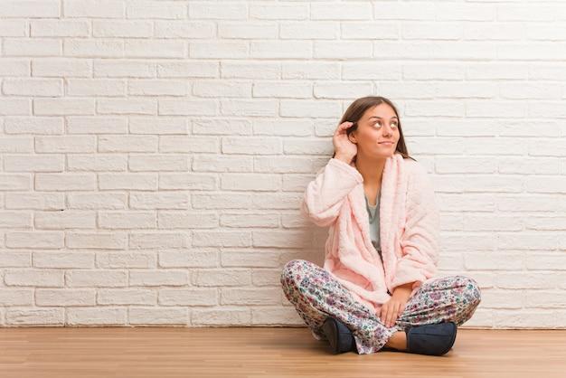 De jonge vrouw die pyjama draagt probeert aan een roddel te luisteren
