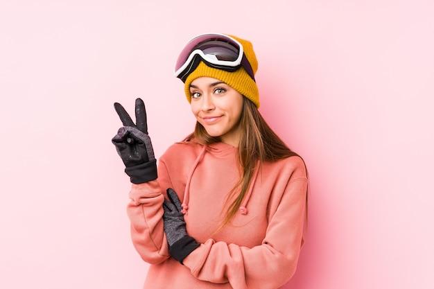 De jonge vrouw die ski draagt kleedt het tonen van nummer twee met vingers