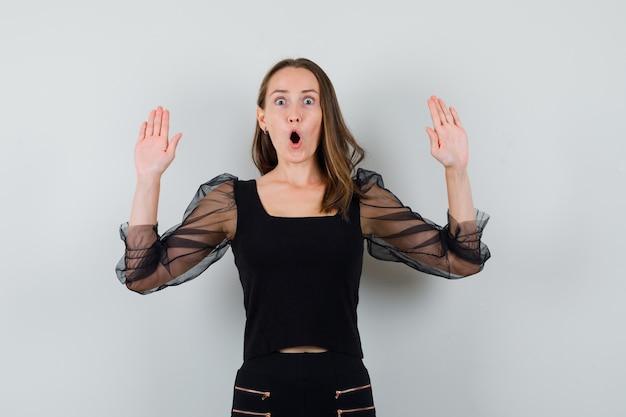 De jonge vrouw die stopgebaar met beide toont dient zwarte blouse en zwarte broek in en kijkt geschokt. vooraanzicht.