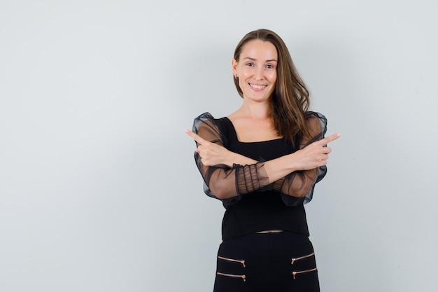 De jonge vrouw die tegengestelde richtingen met beide toont dient zwarte blouse en zwarte broek in en gelukkig kijkt. vooraanzicht.