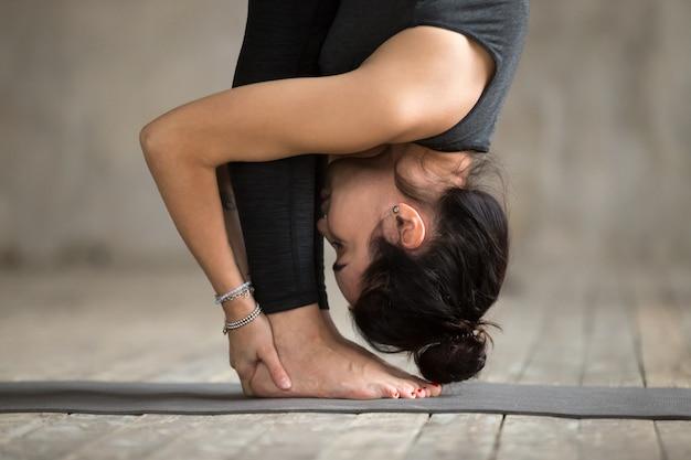 De jonge vrouw die uttanasana oefening doet, sluit omhoog