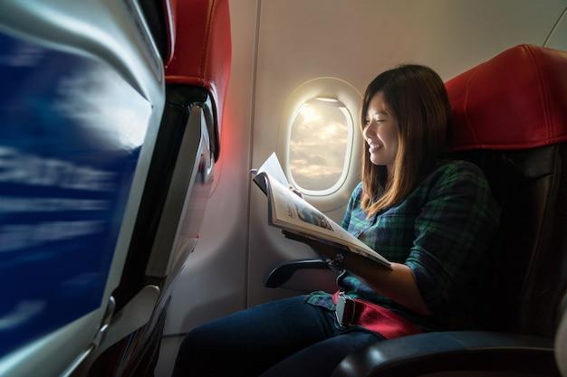 De jonge vrouw die van azië het tijdschrift leest terwijl het reizen binnen het vliegtuig naast windo