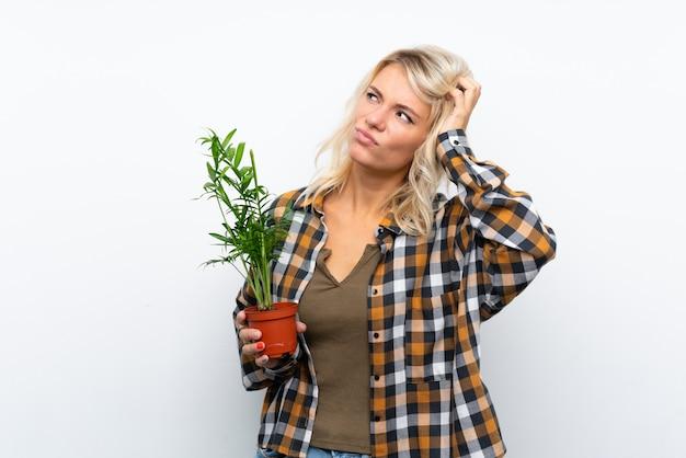 De jonge vrouw die van de blondetuinman een installatie over geïsoleerde witte muur houden die twijfels hebben en met verwarren gezichtsuitdrukking