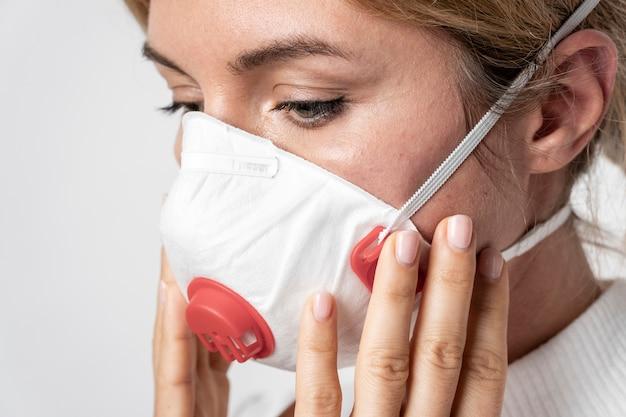 De jonge vrouw die van de close-up chirurgisch masker draagt
