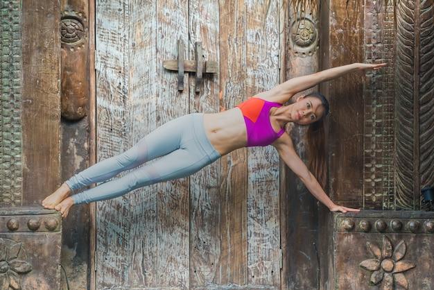 De jonge vrouw die van de sportyoga thuis oefening doet.