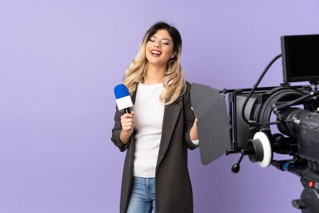De jonge vrouw die van de verslaggever een microfoon houdt en nieuws rapporteert dat op purpere muur met duimen op gebaar en het glimlachen wordt geïsoleerd