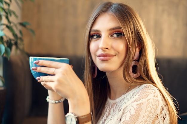 De jonge vrouw die van nice van kop van koffie in een koffiewinkel geniet