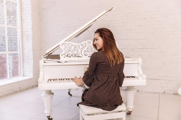 De jonge vrouw die van smilling de piano speelt