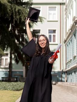 De jonge vrouw die van vooraanzichtsmiley graduatietoga dragen