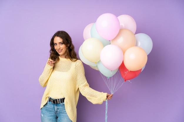 De jonge vrouw die vele ballons vangen over geïsoleerd op purpere muur richt vinger op u