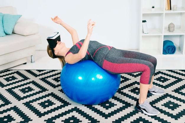 De jonge vrouw die virtuele werkelijkheidsglazen dragen die zich over pilatesbal uitrekken wat betreft dient de lucht in