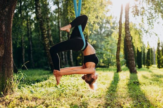 De jonge vrouw die vliegyoga doet bij de boom hangt ondersteboven.