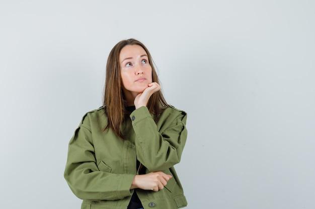 De jonge vrouw die weg kijkt terwijl haar leunt dient groen jasje in en peinzend kijkt. vooraanzicht.