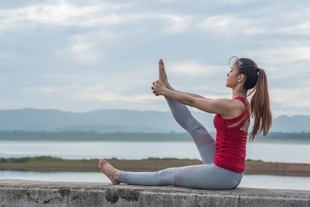 De jonge vrouw die yoga doet stelt in natuurreservaat.