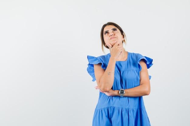 De jonge vrouw die zich in denken stelt stelt terwijl het opzoeken in blauwe kleding en hoopvol kijkt