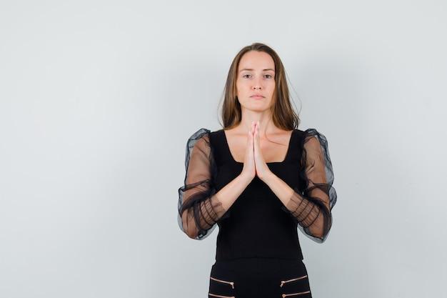 De jonge vrouw die zich in gebed bevindt stelt in zwarte blouse en zwarte broek en kijkt ernstig. vooraanzicht.