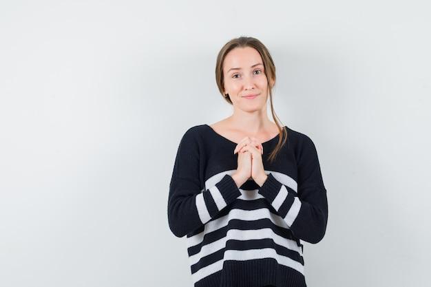 De jonge vrouw die zich in gebed bevindt stelt in zwarte blouse en zwarte broek en kijkt optimistisch