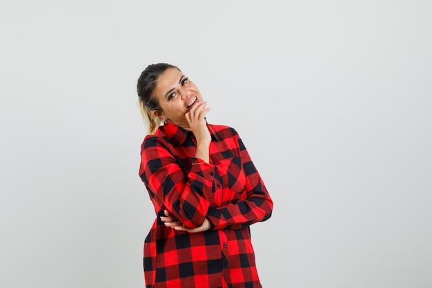 De jonge vrouw die zich in het denken bevindt stelt in geruit overhemd en kijkt vrolijk, vooraanzicht.