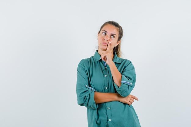 De jonge vrouw die zich in het denken bevindt stelt in groene blouse en peinzend kijkt