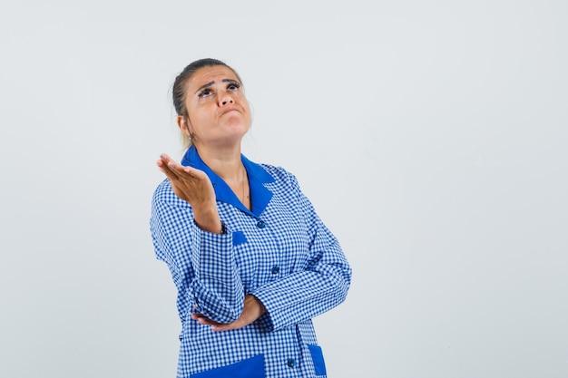 De jonge vrouw die zich in het denken bevindt stelt in het blauwe overhemd van de gingangpyjama en kijkt moe, vooraanzicht.