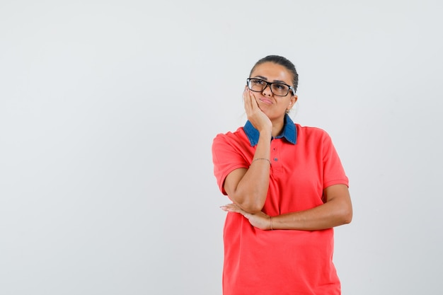 De jonge vrouw die zich in het denken stelt, wang leunt op palm in rood t-shirt en glazen en peinzend kijkt. vooraanzicht.