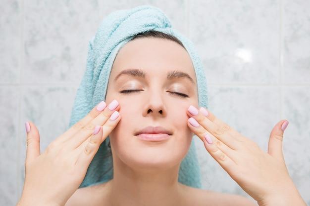 De jonge vrouw doet gezichtsmassage met handen in de badkamers.