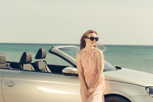 De jonge vrouw drijft een auto op het strand