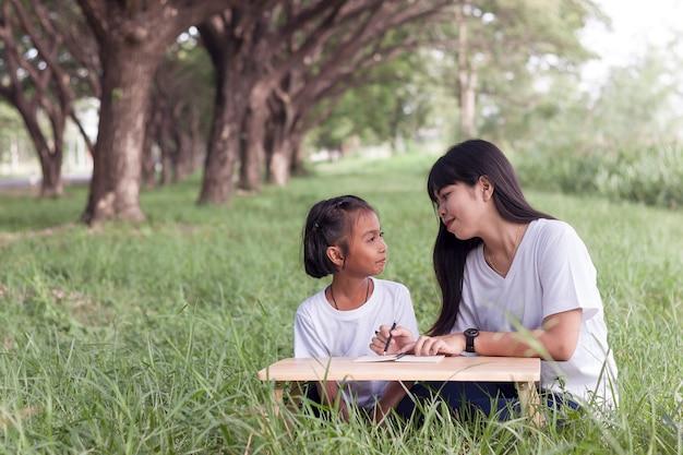 De jonge vrouw en het meisjespret van azië om op gras te leren