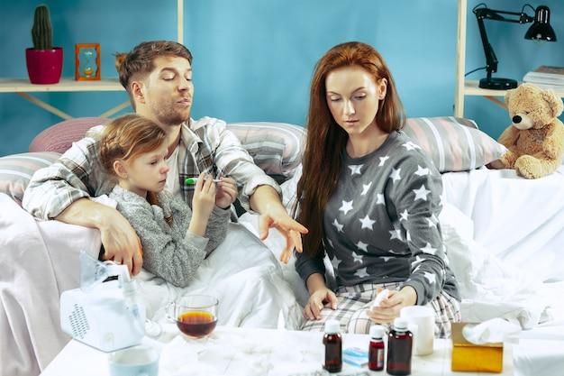 De jonge vrouw en man met zieke dochter thuis. thuisbehandeling. familieleden.