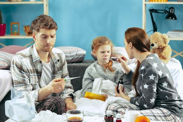 De jonge vrouw en man met zieke dochter thuis. thuisbehandeling. vechten met een ziekte. medische gezondheidszorg. familieleden. de winter, griep, gezondheid, pijn, ouderschap, relatieconcept