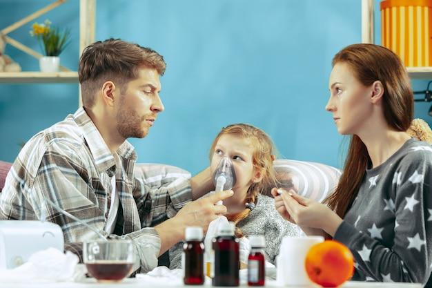 De jonge vrouw en man met zieke dochter thuis.