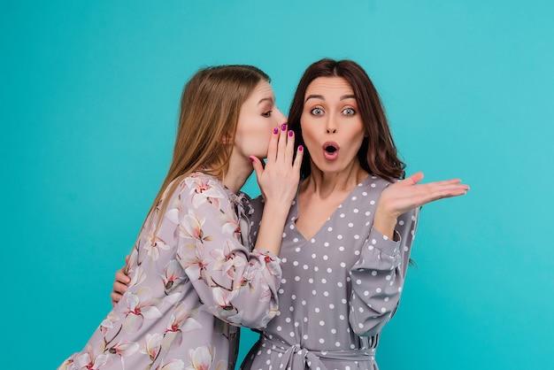De jonge vrouw fluistert een geheim aan haar meisjesvriend die over blauwe achtergrond wordt geïsoleerd