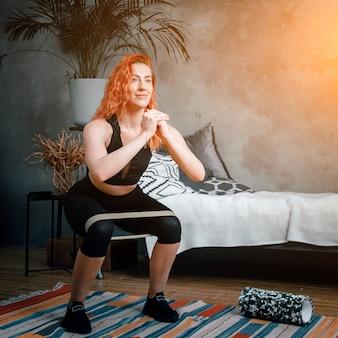De jonge vrouw gaat thuis sporten. vrolijke sportvrouw met rood haar maakt squat met sport fitness elastiekjes in de slaapkamer