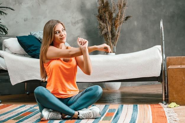 De jonge vrouw gaat thuis sporten
